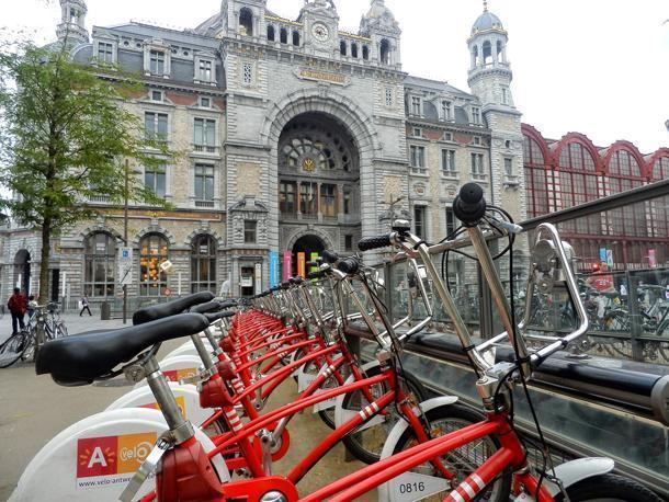 Antwerpen Velo city bikes waiting to be rented in front of Antwerp's Central Station.