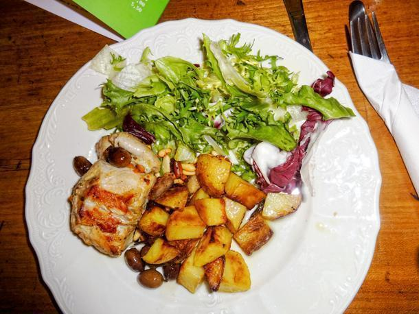 Rabbit cooked with taggiasche olives, pine nuts, potatoes and served with salad