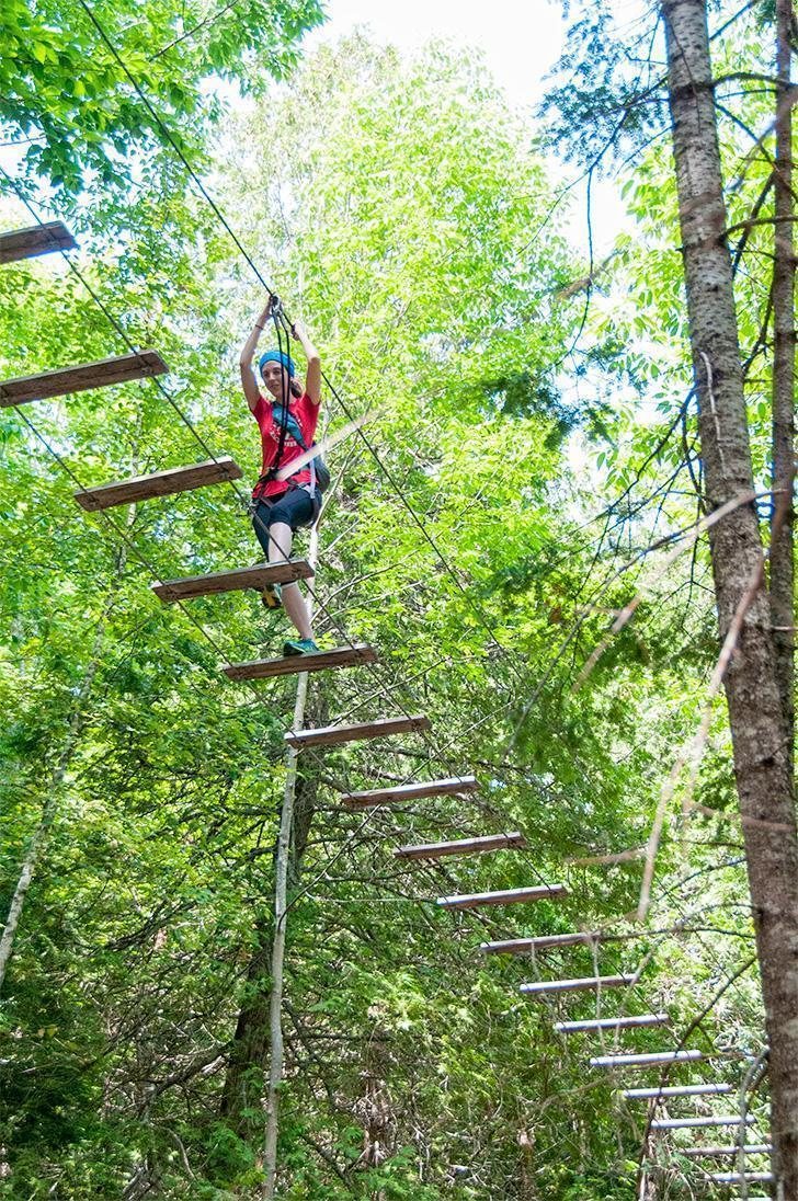 Amy balances among the treetops at TreeGO Mactaquac, near Fredericton, New Brunswick