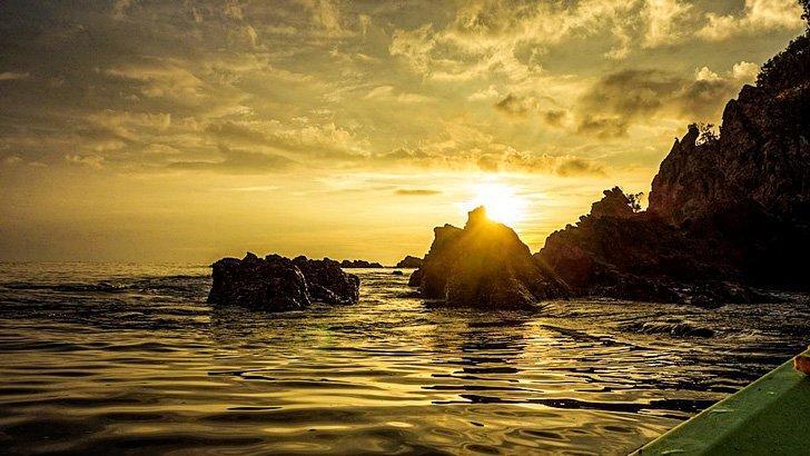 Enjoy a sunset boat cruise on Koh Phayam island, Thailand.