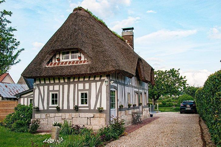 Timber-framed houses with thatched roofs are a common sight in Normandy, France.